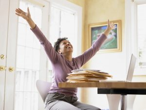 %name Middle aged woman celebrating at her desk